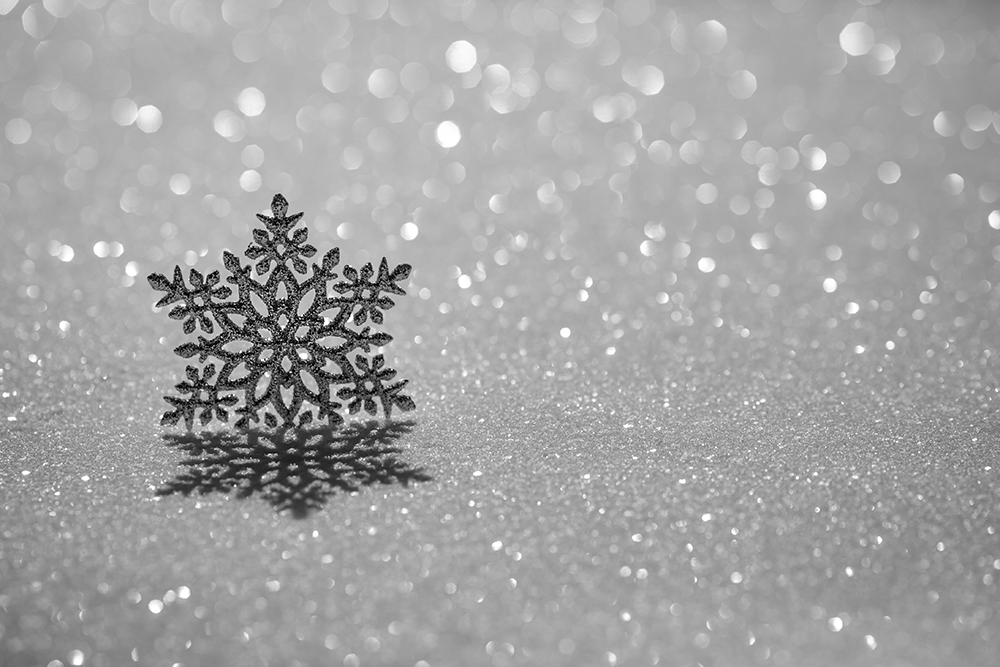 Christmas ornament on snow against blurred lights background