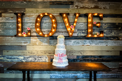 A wedding cake and a love sign at a wedding reception