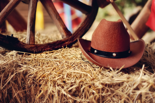 A cowboy hat on a bale of hay like you might find with a mechanical bull